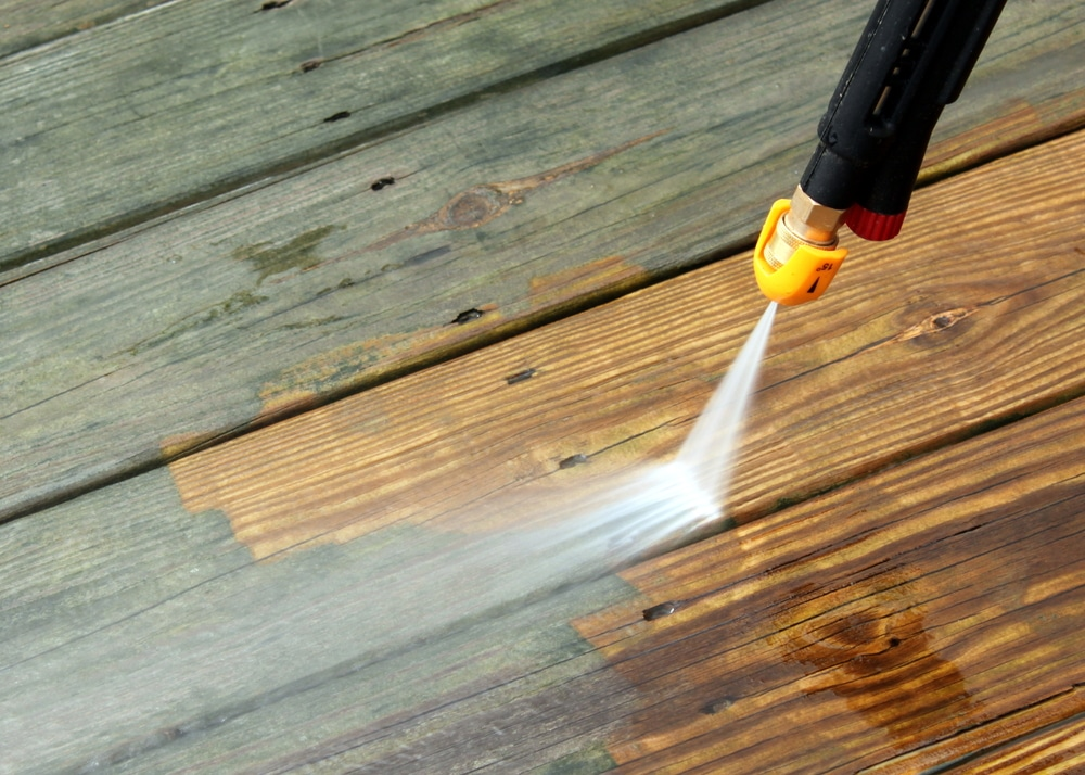 Pressure washer being used to clean decking
