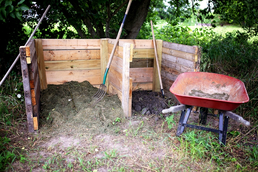 two compost piles in garden with red wheelbarrow