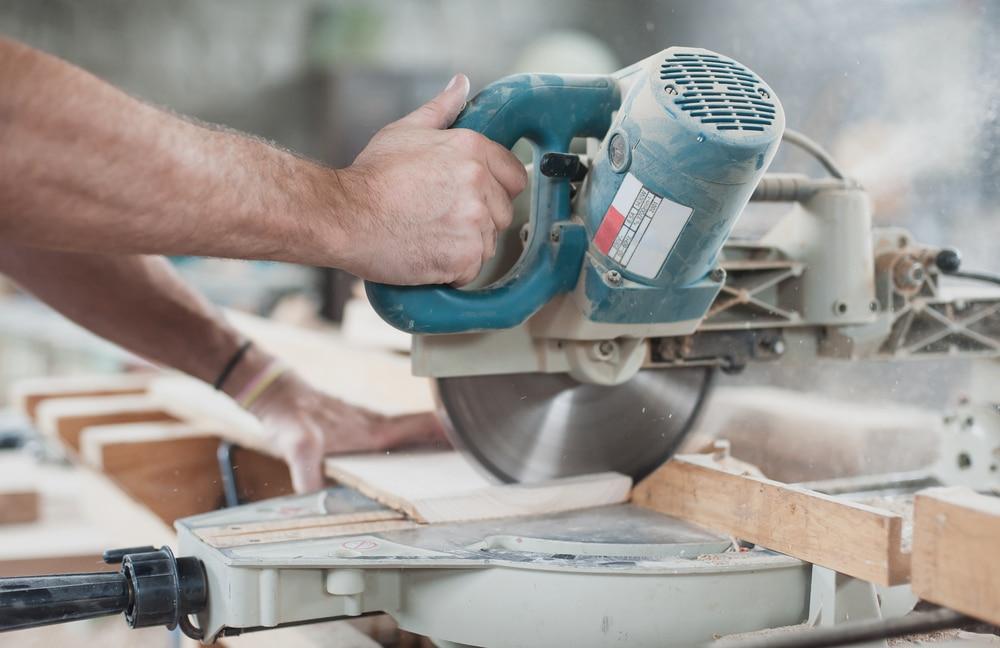 carpenter cutting wood with circular saw