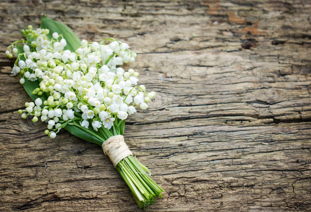 A beautiful bouquet on wooden background featuring Lily of the Valley