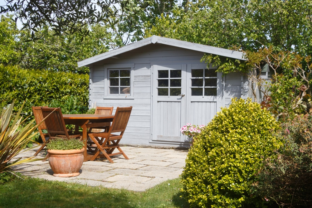 light blue shed in garden with outdoor furniture