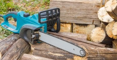 electric chainsaw sat on pile of logs