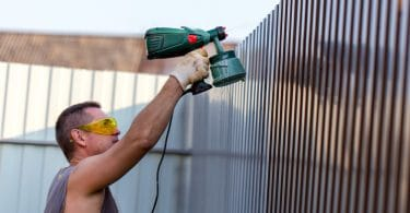 man painting a metal fence