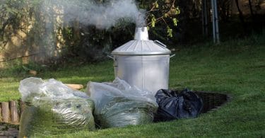 garden incinerator with bags of lawn cuttings