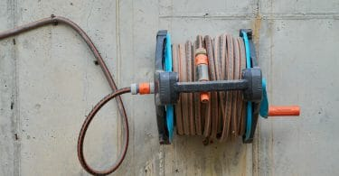 a wall mounted garden hose that has been retracted