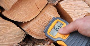 man measuring moisture content of logs