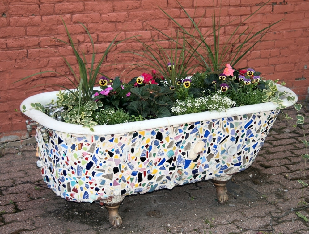 A repurposed and heavily painted bathtub full of plants