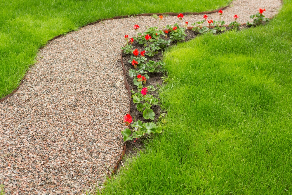 A stunning gravel path winding through a garden lawn
