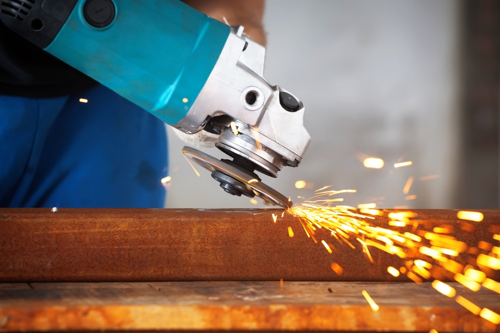 an angle grinder sawing into metal