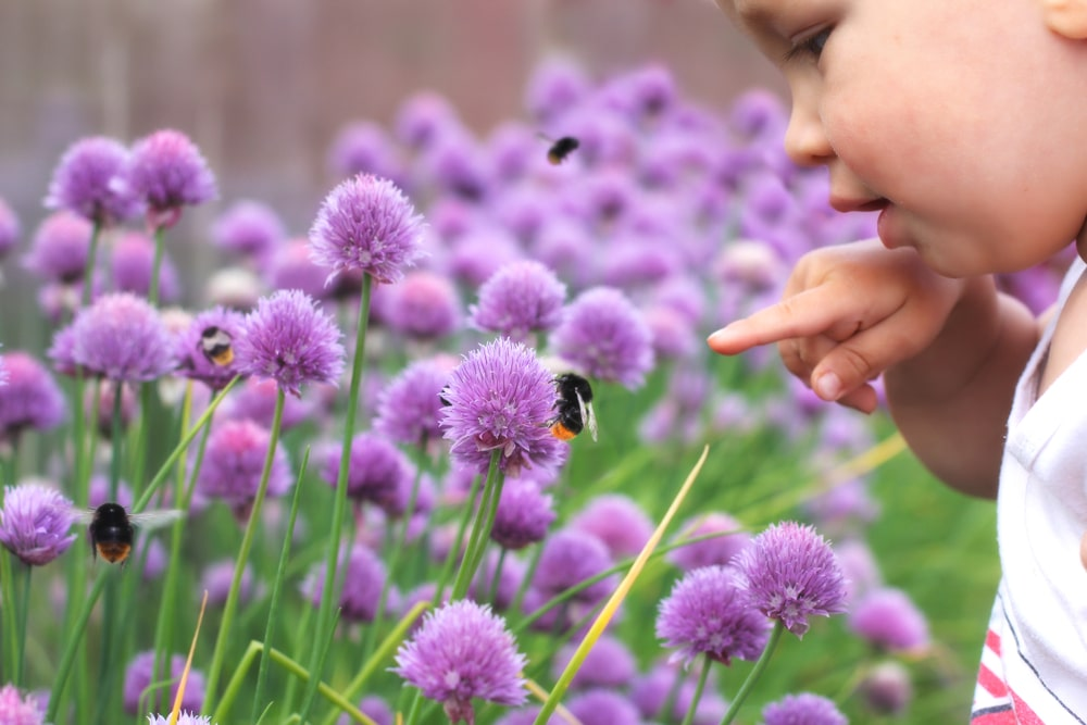 A small child points a finger at a bumblebee on a flower