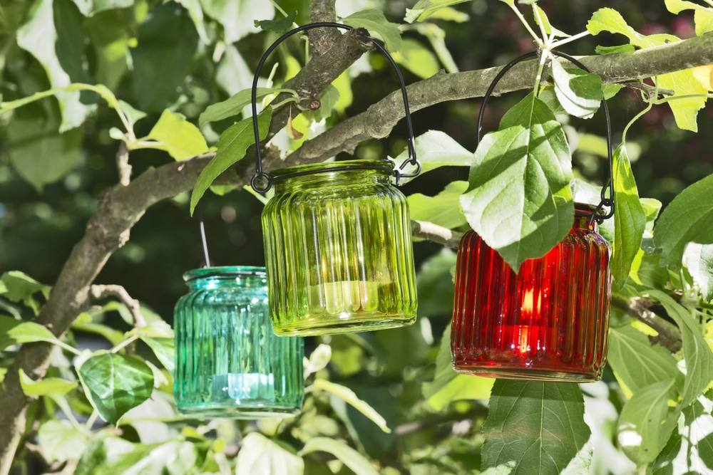 glass jar lanterns hung from tree branches