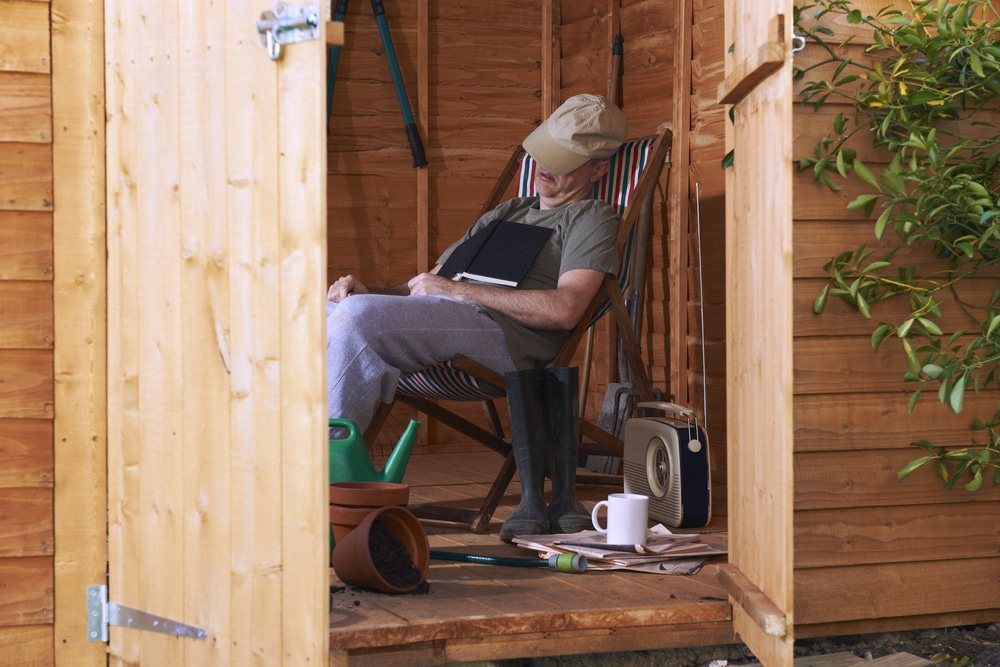 man asleep in shed with hat over face