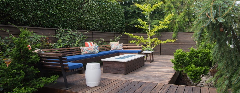 a decked garden area with table and seating