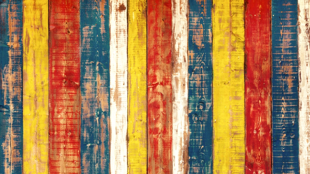 fence painted in blue, white, red & yellow stripes
