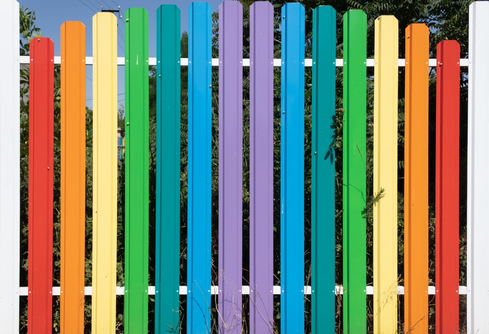 metal fence painted in colours of the rainbow