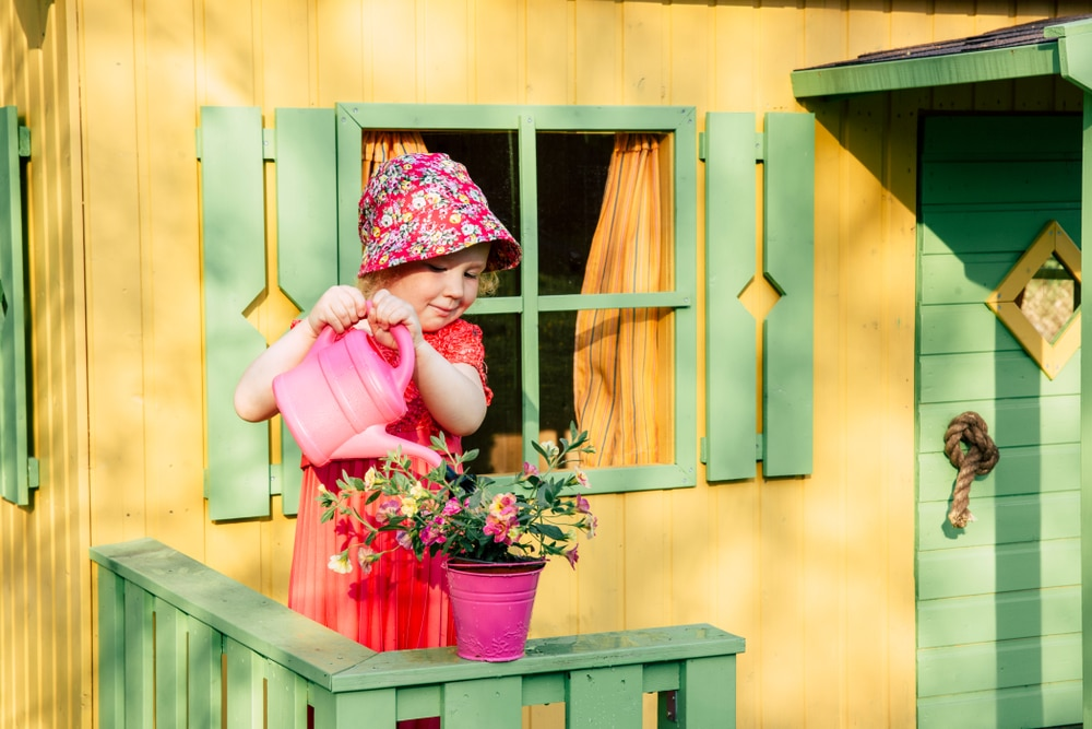 young girl watering a plant pot outside her playhouse