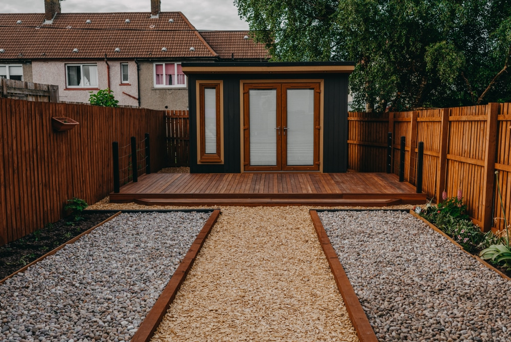 a black garden office with decking and gravel
