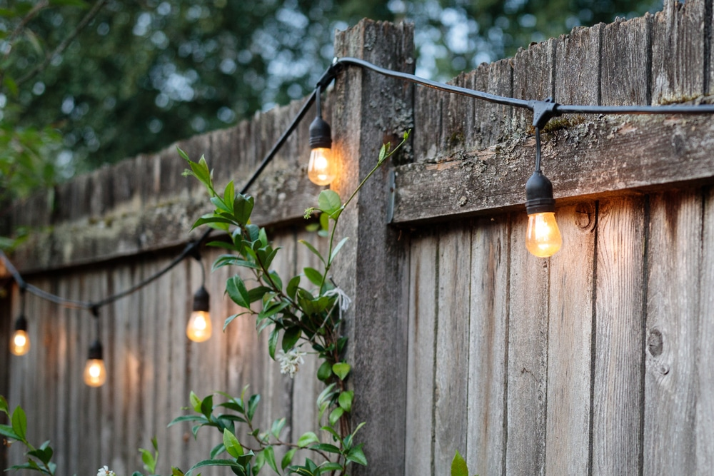 timber fence festooned with lighting