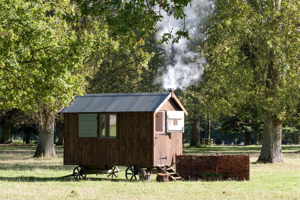 A traditional shepherd's hut with a smoking chimney