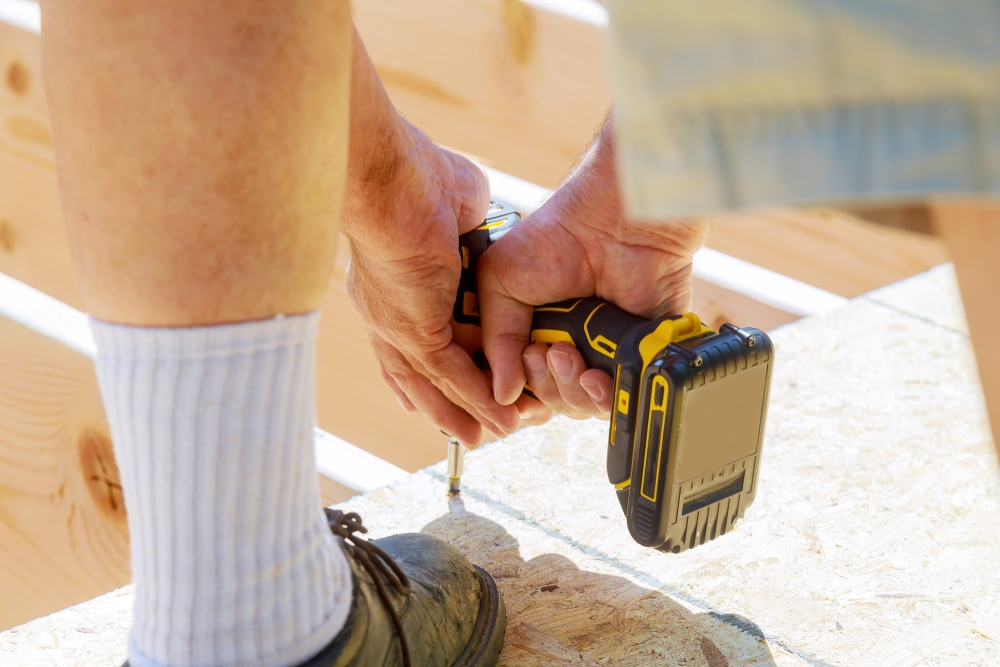 man drilling screws into decking frame