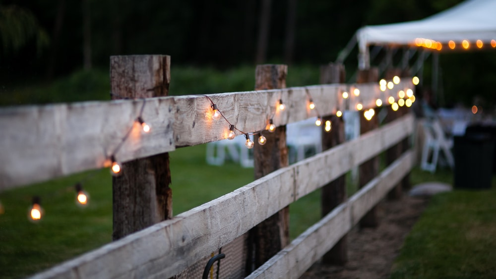 timber fence covered in fairy lights