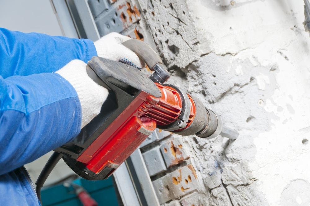 workman breaking down a wall