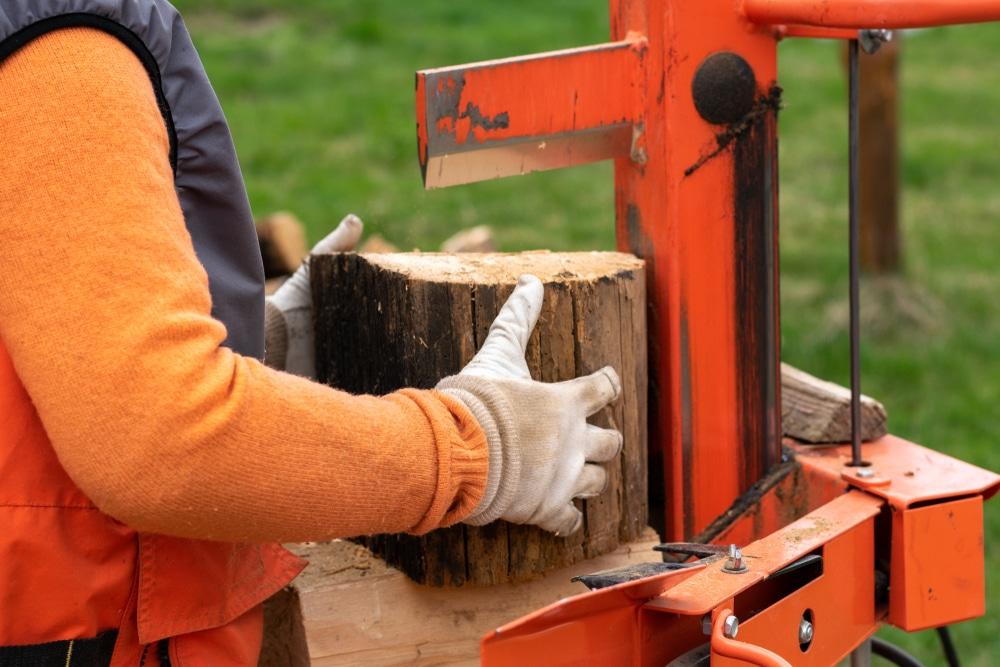man positioning log on an electric splitter