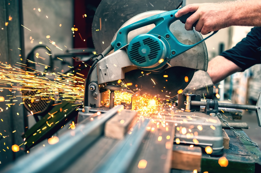 worker using a mitre saw to cut into metal and plastic