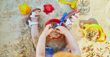 toddler playing in sand