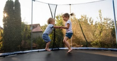siblings having fun jumping on a trampoline