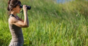 women staring out of binoculars with greenery in background