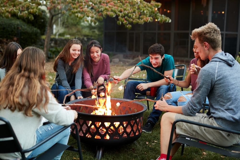 teenagers sat around a garden fire pit