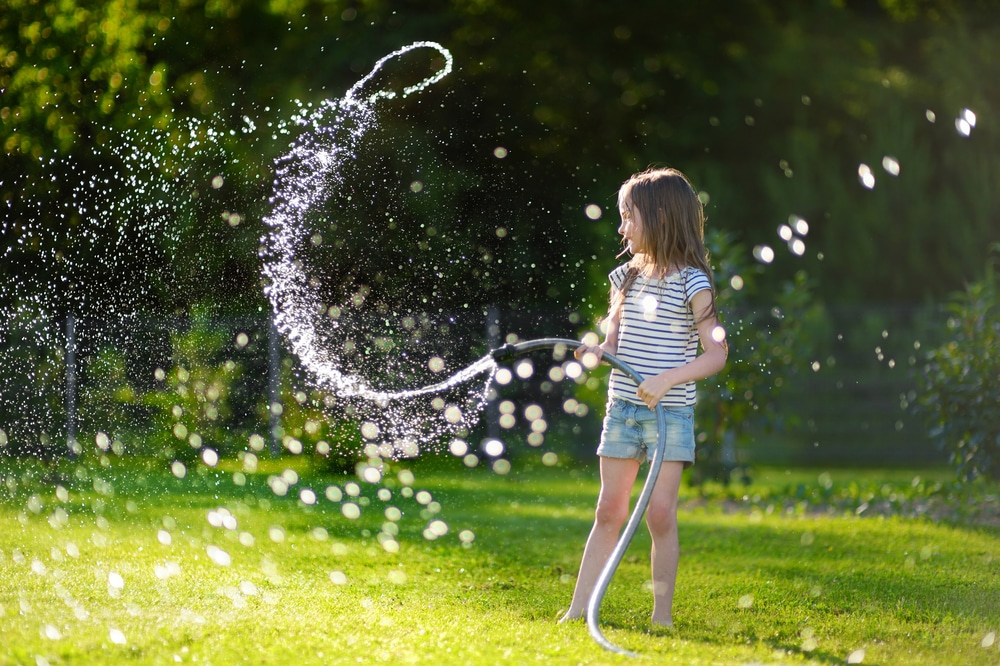 young girl playing with garden hose on lawn