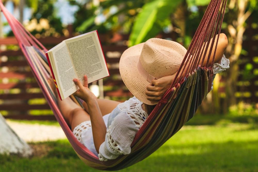 woman laid in garden hammock reading