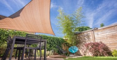 garden shade sail sat over decking and garden furniture