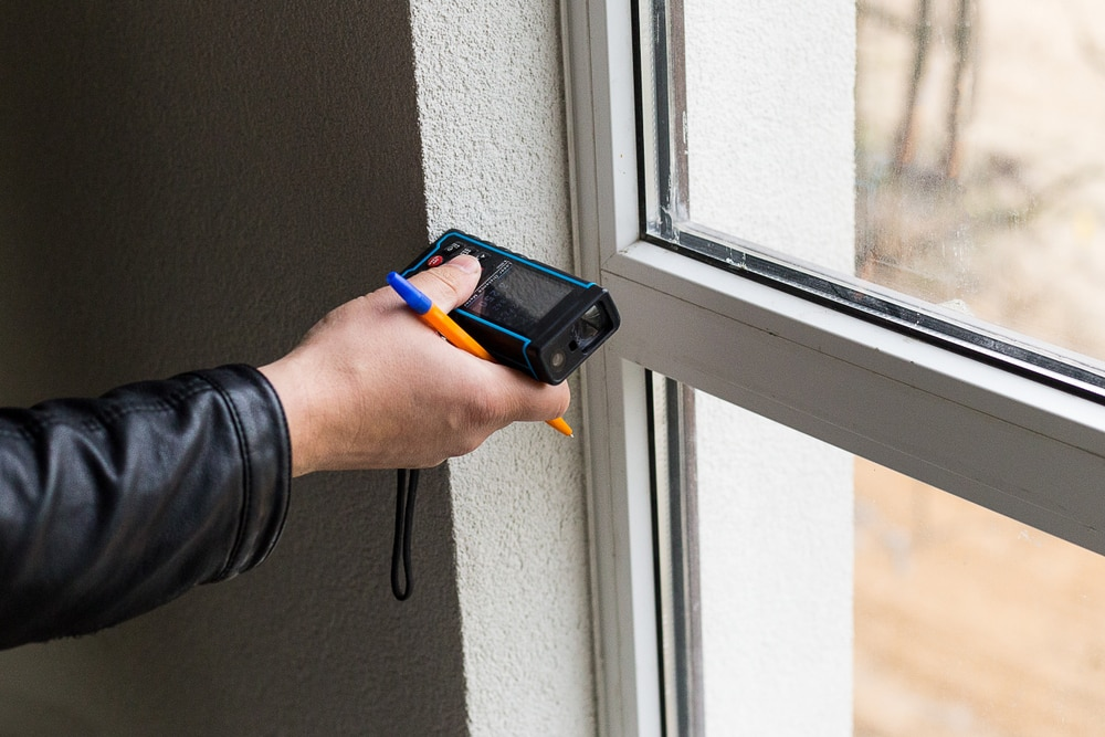 laser measure being used on window