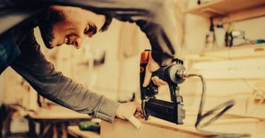 man using nail gun on workbench
