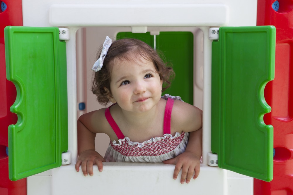 young girl looking out of window of playhouse
