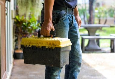 man carrying a black and yellow toolbox