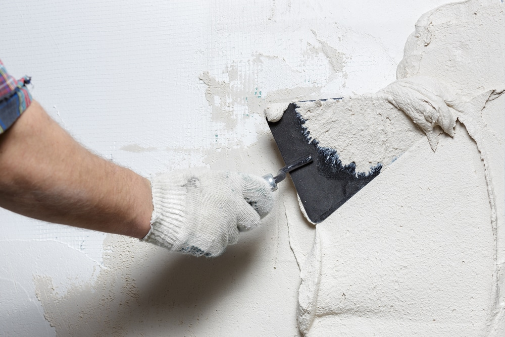 construction worker plastering a wall with a trowel