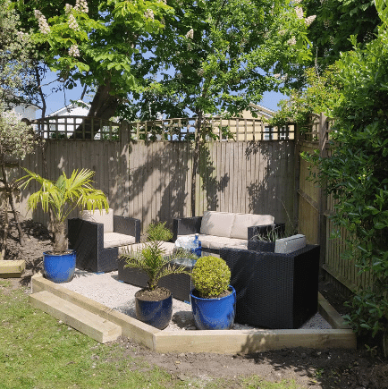 clean lawn with raised area for garden furniture, covered by a tree