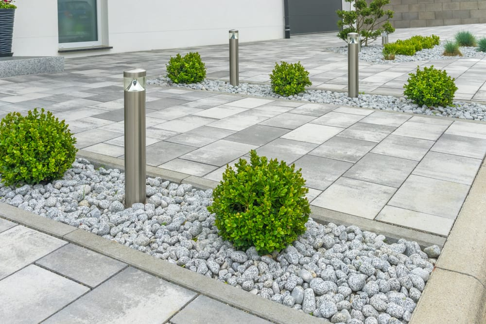 front garden with grey paving, pebbles and miniature bushes