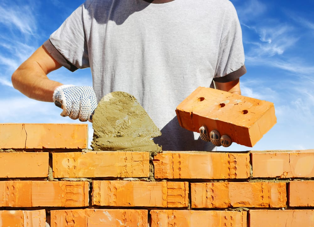 man in grey t-shirt laying bricks