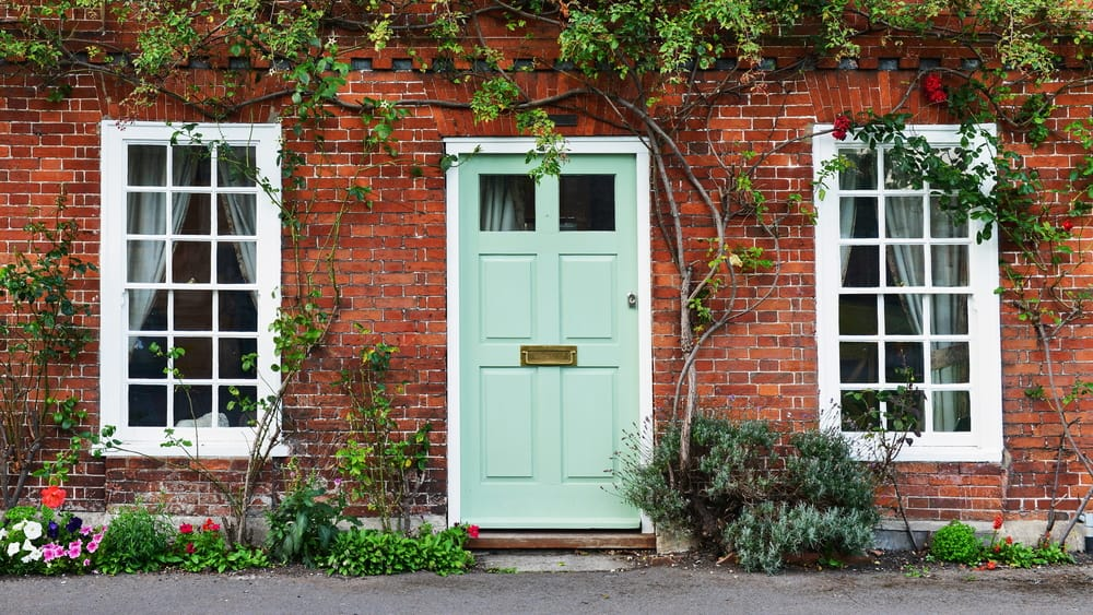 exterior of a house on a london street, including green door and climbing plants on brick
