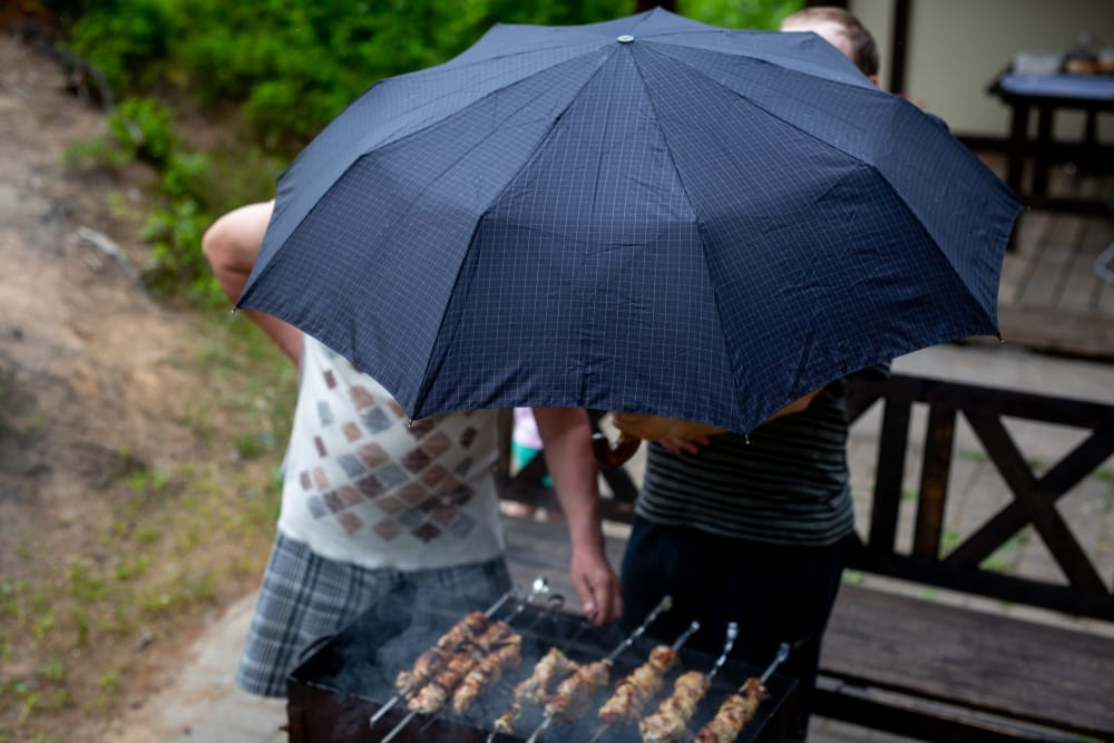 people stood over a bbq sheltering from the rain with their blue umbrella
