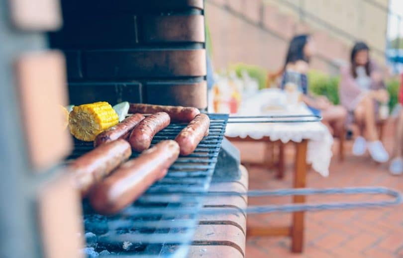 sausages and corn on the cob grilling on a brick barbeque