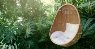 rattan egg chair sat in front of garden greenery