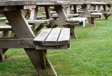 wooden benches on the grass lawn of a pub
