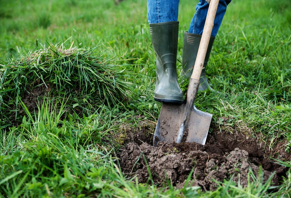man in green wellies digging turf with a spade