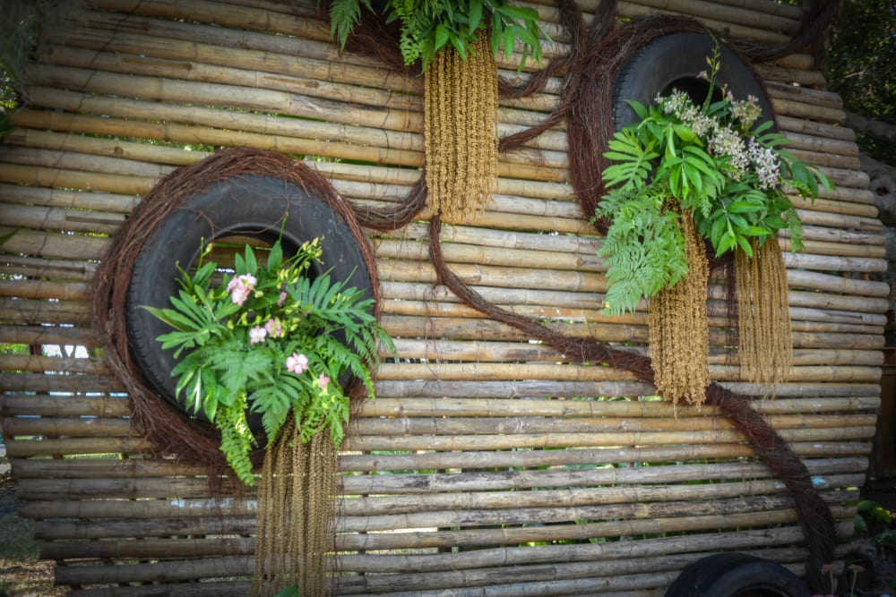 tyre planters hung from bamboo in a vertical garden